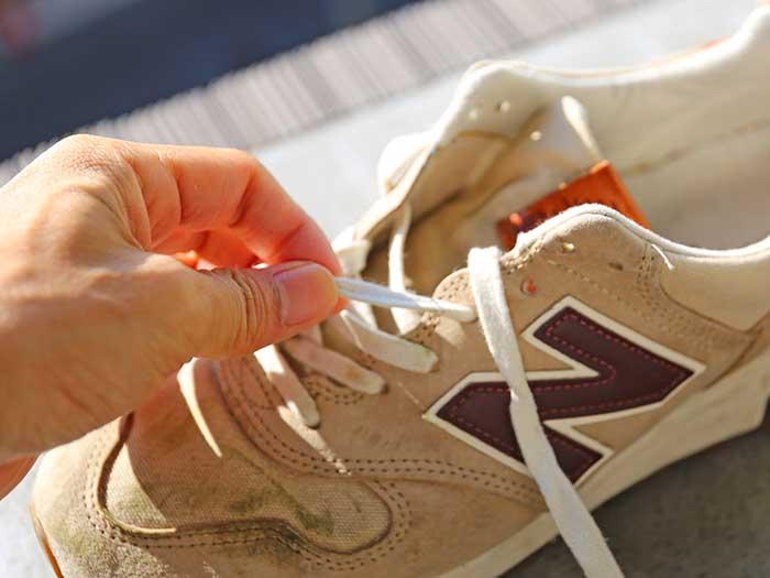 汚れたスニーカーの靴紐を外す