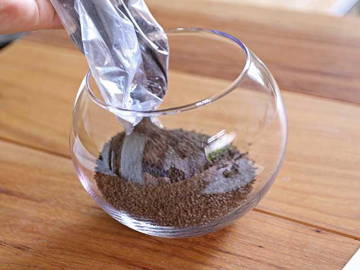 洗ったガラスボトルにソイルを入れる