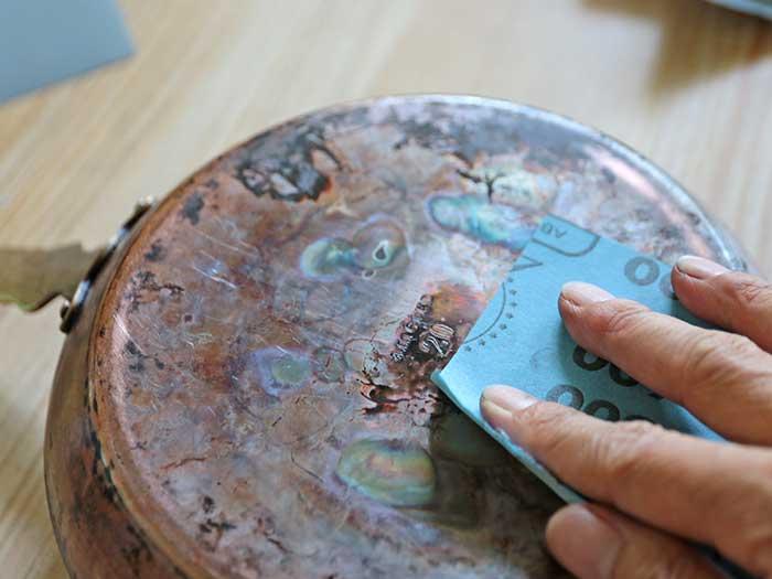 銅のフライパンの変色部分を紙やすりで磨く