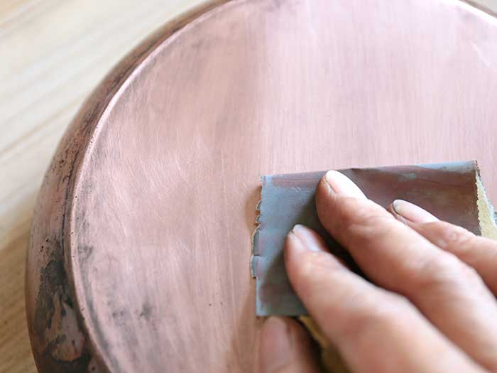 目の細かいやすりで銅のフライパンを磨く